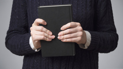 Woman's hands holding a black book, gray background
