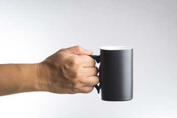 Hand hold dark cup of drink