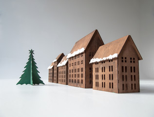 Wooden toys. Miniature houses and Christmas tree on white background.