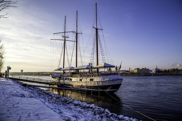 Schiff am eingeschneiten Rheinufer bei Mainz im Winter