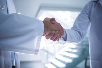 Mid section of doctors shaking hands in corridor