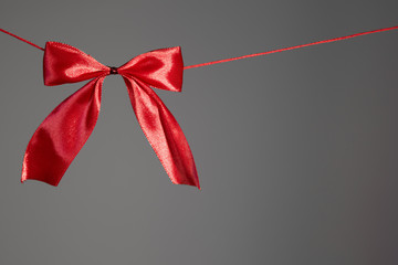 Beautiful holidays red satin bow on gray background