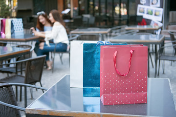 shopping bag on the table,two friends shopping in background in
