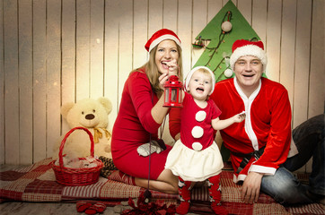 Happy family in Santa's cloth with snowman baby near Christmas tree and toys. Father, mother and baby