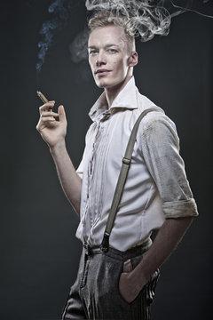 Junger blonder Mann in 20er Jahre Kleidung raucht Zigarre