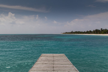Steg im Meer vor tropischer Insel