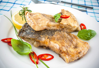 Fried fish on white plate and fork, knife
