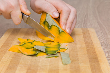 Hands peeling the piece of pumpkin with knife on the wooden board in the kitchen.Healthy eating and lifestyle.