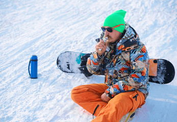 Men with beard vaping outdoor in sunglasses, sitting on snow
