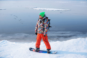 snowboarder standing on the top of a mountain on the background of frozen lake in winter