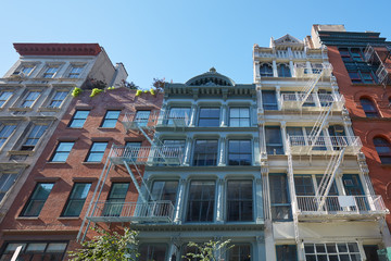 New York houses facades with fire escape stairs, sunny day in Soho