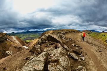 woman hiker on the trail in the Islandic mountains. Trek in National Park Landmannalaugar, Iceland