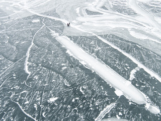 Three people walking across icy frozen lake, elevated view