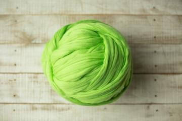 Green merino wool ball on wooden background