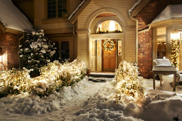 Christmas decorations and lights line front path and patio in the snow