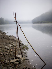 Tripod of twigs on riverbank
