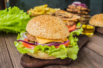 Great Hamburger and french fries on a wooden table in rustic style. Close-up