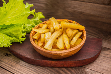French fries on a wooden plate with greens. Close-up