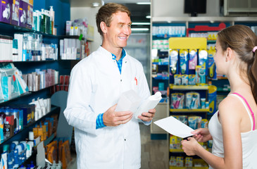 portrait of man druggist in white coat giving advice to customer