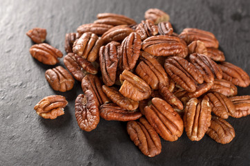 Peeled pecan nuts on a slate plate, selective focus