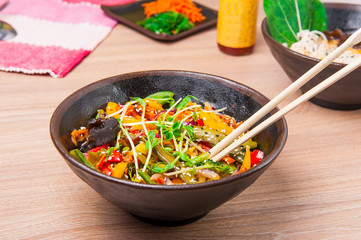 Traditional chinese wok dish vegetables in a sweet - sour sauce garnished with soybean sprouts in  round plate