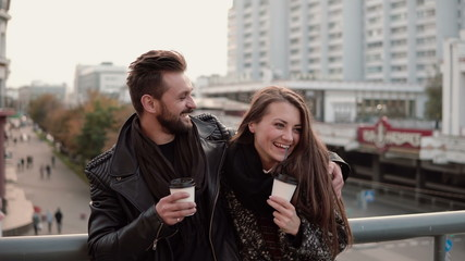 Beautiful girl comes to the handsome young man. they are friendly hug laugh joyfully, holding takeaway coffee.