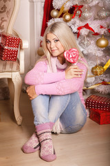 Beautiful gril at christmas tree with gifts new year