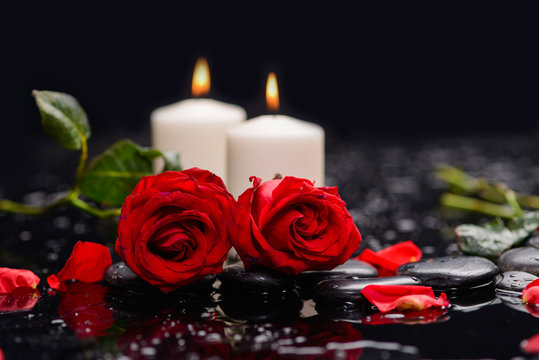 Two red rose with candle ,green leaf and therapy stones