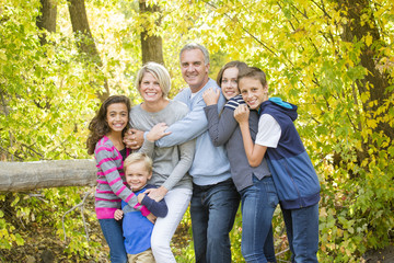 Fototapeta A smiling, happy, large beautiful family portrait. Standing together and hugging each other outdoors with a forest in the background obraz