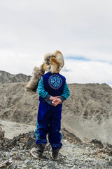 cute boy portrait of Kazak family : Mongolian is wearing fox hat .on  mountain,.
