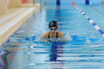 Young girl in goggles and cap swimming butterfly stroke style in the blue water pool.
