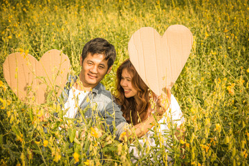 asian couple holding heart symbol in yellow field at summer time