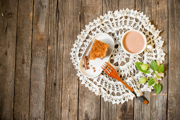 Two cups of cocoa, jug of milk, donut on a saucer, round lacy napkin. two wooden spoon. Cake on the plate. View from above