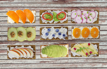 Sandwiches with cream cheese and fresh berries, fruits and vegetables. Fresh healthy appetizer snack with crispbread.