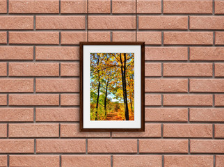 Brown wooden frame with colorful autumn motif picture, hanging on cords against red bricks background. Gallery style design, rustic home decoration mock up