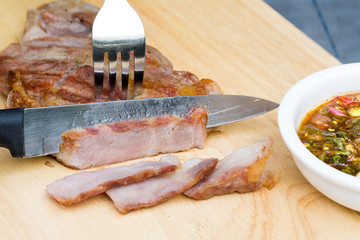 Sliced grilled pork with black pepper on the chopper wood with k