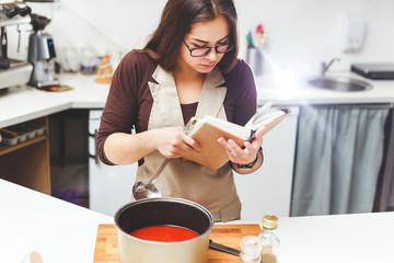 Girl preparing tomato soup recipes according to the book.