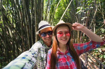 Couple make selfie on camera in jungle. Travel concept.