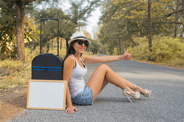 Beautiful woman who is doing the auto-stop along the road with white desk for your text.