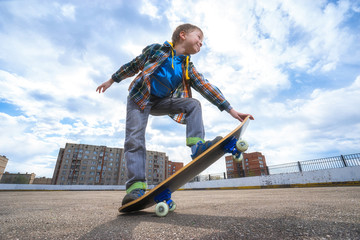 Happy child is going to skateboarding - people, sport and skateboard concept.