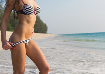Young sexy woman in swimwear on the beach.