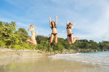 Summer holidays and vacation - happy girls jumping on the beach.Tropical vacation.