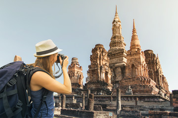Hiker with backpack taking picture  in Sukhothai, Thailand. Travel concept.