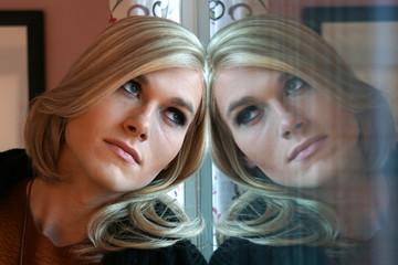 Nachdenkliche Frau (Gender) am Fenster
