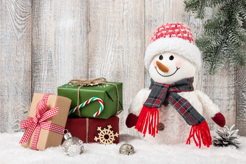 Snowman and gift boxes on snow
