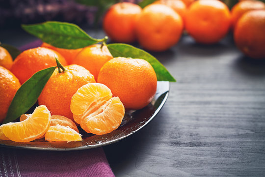 Fresh clementines with leaves served on plate, on black wooden table. Copy space