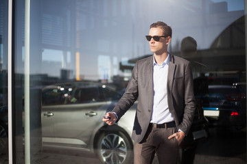 Businessman holding car keys standing outdoor next to window, cars at the background