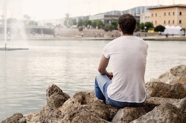 Mann sitzt am See und schaut in die Ferne