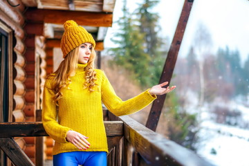 young girl in a winter sweater stretching out her hands to the snow