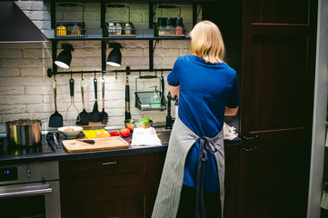 woman housewife setting the table. young blonde in a dress and apron, served in a dining table, puts the dishes, doing the work in the kitchen.